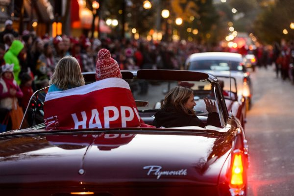 Children riding in the back of a vintage car huddle under the cover of a banner with the phrase, Happy Homecoming, as they wave to thousands of spectators lining State Street during the University of Wisconsin-Madison's Homecoming Parade on Oct. 16, 2015. The annual parade is one of many Homecoming week activities sponsored by the Wisconsin Alumni Association (WAA). (Photo by Jeff Miller/UW-Madison)