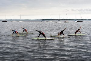 A group of women maintain balance during an Outdoor UW standup paddleboard (SUP) yoga class